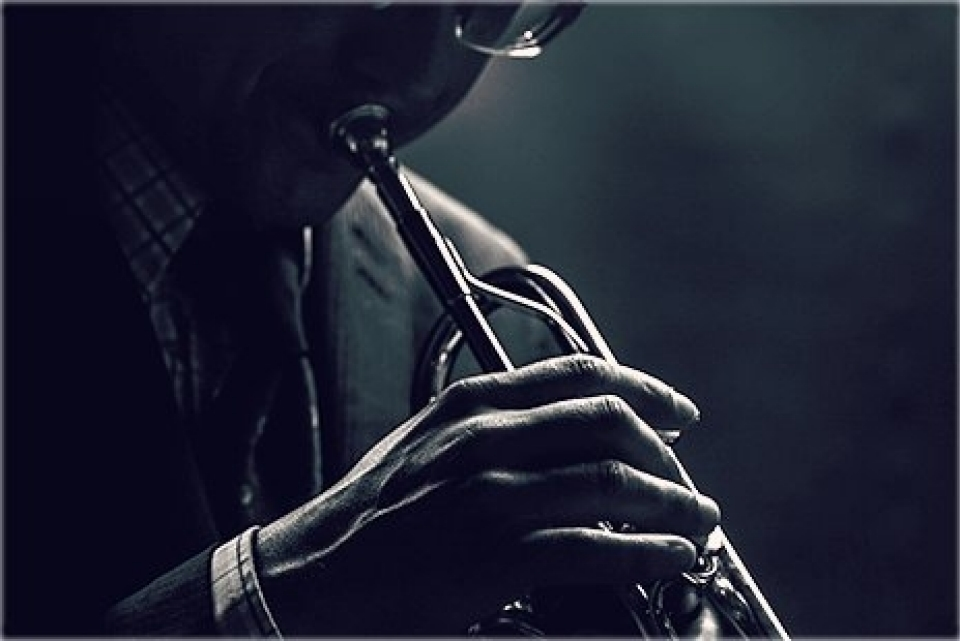Musician playing trumpet over black background