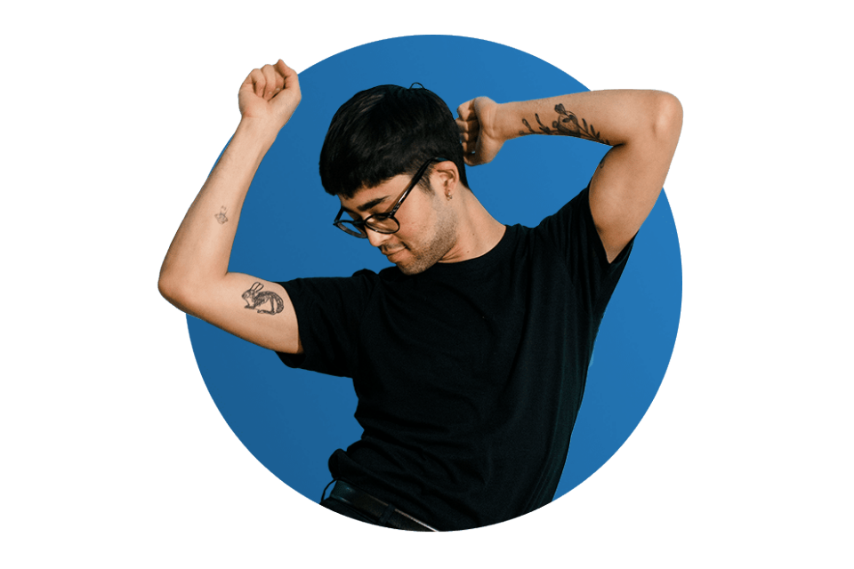 Man with tattoos and glasses dancing