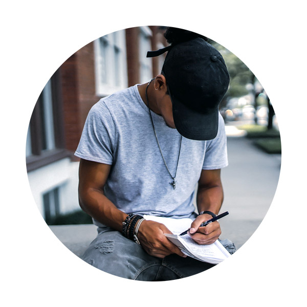 man sitting outside and writing in a notebook